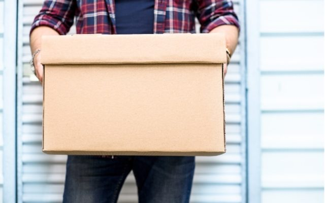 Young man holding a moving cardboard box in front of a storage door.Life style, storage, moving, storing, organizing concept. Space to write