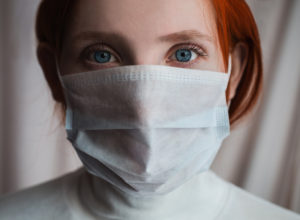 red-haired girl with a medical mask on a white background, woman, doctor, European, woman in a white turtleneck
