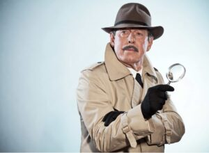 detective man with mustache and hat. Holding magnifying glass