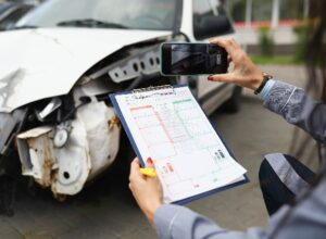 Insurance agent takes pictures of crashed car on his smartphone and fills out the insurance